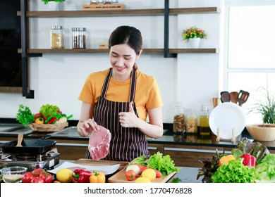 Asian women present fresh food. Shot housewife showing thumb up trying to cooking and showing pork steak in kitchen in house to take picture for sell food box online. Work from home / covid19 concept