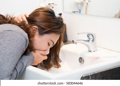 Asian women puking in the bathroom