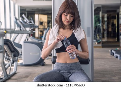 Asian women put sport wear thirsty water and open bottles pure water  after exercise in gym Fitness, sport, people, exercising and lifestyle concept
