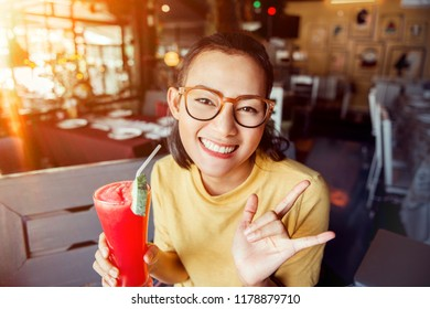 Asian women raise their glasses and smile.focus on face