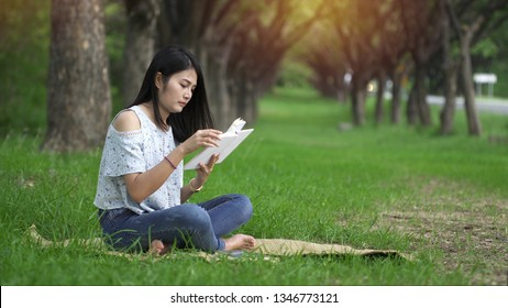Asian women read books at the park happily.