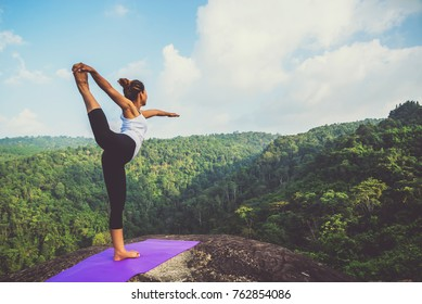 Asian women relax in the holiday. Play if yoga. On the Moutain rock cliff. Nature of mountain forests in Thailand