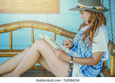 Asian women relax in the holiday. sit read a book on a wooden swing. Home Front porch. In Thailand
