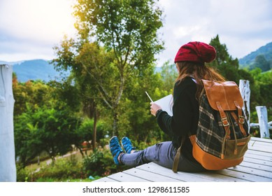 Asian women relax in the holiday. Study read a book. Read a book In the garden on the Moutain. In Thailand