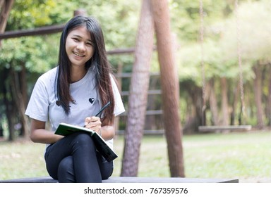Asian women relax in the holiday, Study read a book in park.