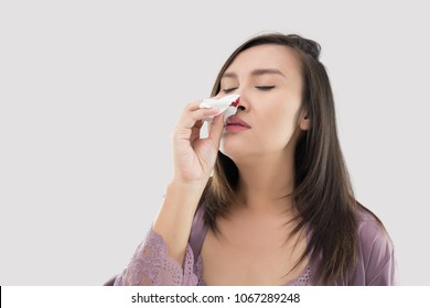 Asian women in satin nightwear with nosebleed against gray Background, The Asian people hurts her nose