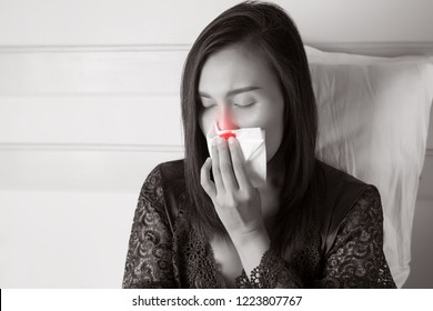 Asian women in satin nightwear with Nosebleed or Epistaxis against gray background, Nasal cavity, The asian people hurts her nose