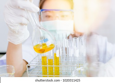 Asian women scientist with test tube making research in clinical laboratory.Science Oil pouring, Formulating the chemical for medicine,Laboratory research, dropping liquid to test tube