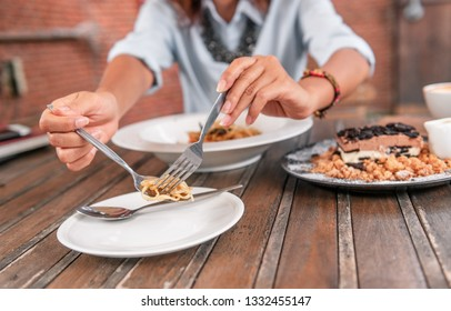 Asian women are scooping food into the plate.Focus on hand