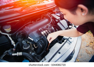 Asian women self car engine oil level check up before go trip