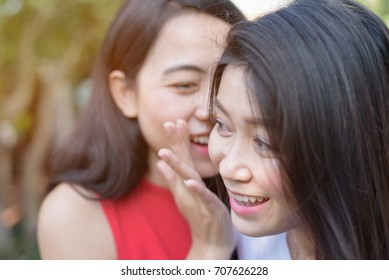 Asian women sharing, gossiping and whispering secrets with best friend  - close up face of people, communication and friendship concept
