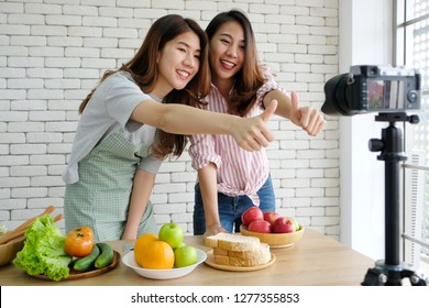 Asian women shoot video,Two young asian woman food bloggers thumb up while recording video, Asia food blog shooting healthy food content such as bread, fruit and vegetable with happiness