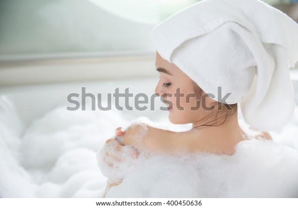 アジアの女性が浴槽にシャワーを浴びている