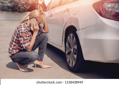 Asian women sitting face to her car talking on the phone after his car is scratched.Focus on hand
