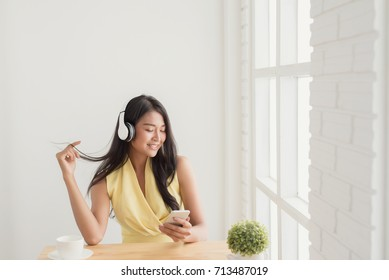 Asian women sitting to relax and  listening music in wireless headphones at the cafe,holding  smartphone in hand