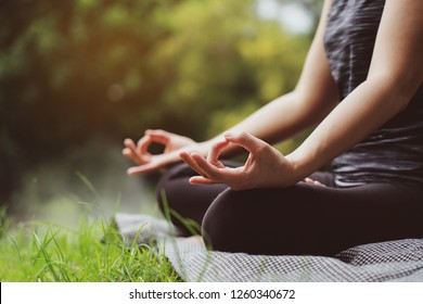 Asian Women sitting in yoga In the garden. On holiday season of the summer Relaxing muscles meditating with nature. Bright sunshine The body is getting healthy vitamin. close up for hand