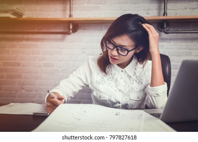 Asian women skepticism when looking down at the paper,Focus on hand