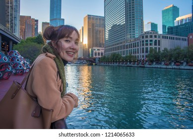 Asian women stand in the City of Chicago downtown and Chicago River with bridges during sunset.