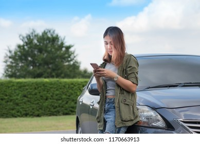 Asian women standing outside the car Calling for help