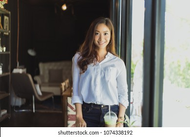 Asian women standing smiling and happy Relaxing in a coffee shop after working in a successful office.