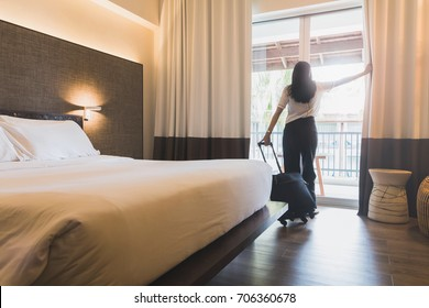 Asian women are staying in a hotel room. Open the curtain in the room Along with carrying luggage