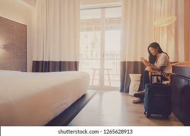 Asian women are staying in a hotel room.Sitting and using smartphone with luggage.Vintage tone.Travel and journey concept.