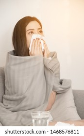 Asian women with stress that suffer from allergies and close the nose with tissue paper. Because of having sneezing all the time .