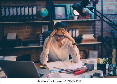 Asian women are stressed out of work. She is in the office at night