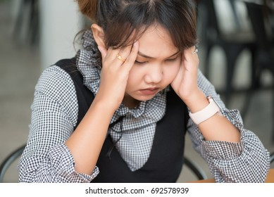 Asian women are stressed out of work in selective focus.