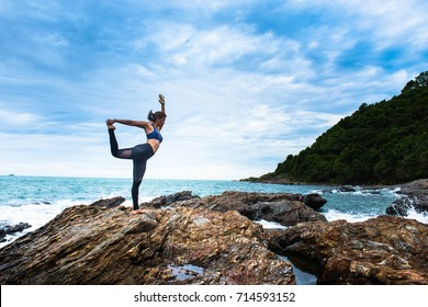 Asian women stretching and practices yoga in Standing bow pulling pose on the rock at the sea beach. Healthy lifestyle and fitness concept. Selective focus. - Shutterstock ID 714593152