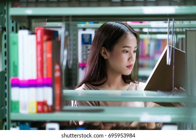 Asian women students books are selected from the bookshelf