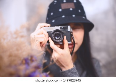 asian women take photo with vintage camera focus at camera