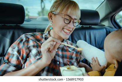 Asian women are taking care of their son in her car.Focusing on the mother's face