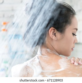 Asian women are taking a shower in the bathroom she is rubbing soap,she is rubbing her back