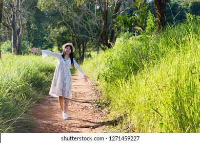 Asian women, Thai people, long hair, wearing hats and dresses, are stretching their arms and are smiling happily in the forest of Khao Yai National Park, Thailand in the daytime. with Copy space