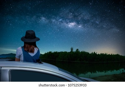 Asian women tourist standing in a sunroof car watching the sky and the Milky Way at night