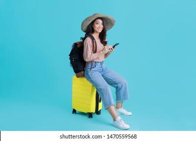 Asiatische Touristen, die sie am Flughafen sitzt. Sie benutzt ein Mobiltelefon.