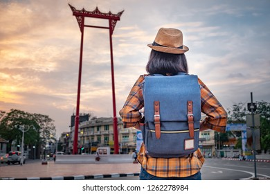 asian women tourists are watching the beauty of The Phram Giant Swing with the sky. It is a beautiful place and a landmark of Bangkok Thailand.