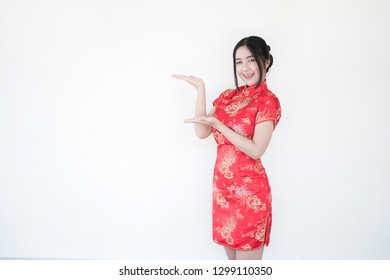 8cad44727b8215 Asian women in traditional Chinese cheongsam dresses with a welcoming  gesture on a white background.