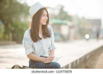 Asian women travel relax in the holiday.sit write a note.