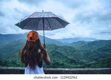 Asian women travel relax in the holiday. The women stood in rain umbrellas on the mountain. During the rainy season.Thailand
