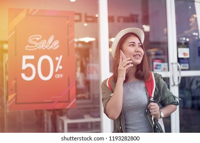 Asian women travel shopping.Asian woman using the smart mobile phone for talking with friend to buy some clothes beside in store shop with happy action at department center