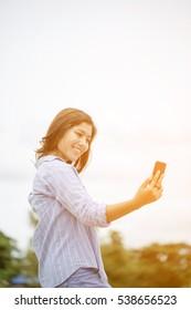 Asian women use smart phone self photograph,selective focus