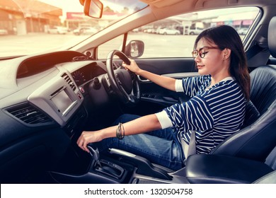 Asian women are using car gear to drive forward when she is in the car intently.focus on face