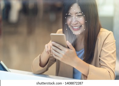 Asian women using the cell phone for access control by face recognition in private identification step when online shopping with the credit card, credit card mockup, online payment concept