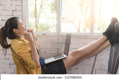 Asian women are using a laptop. She is smiling happily with the online sales that have been well received. From customers around the world. She was sitting by the window in a small cafe.