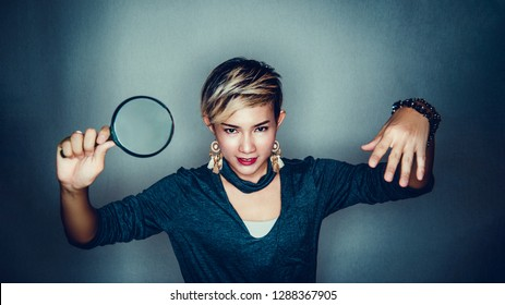 Asian women are using a magnifying glass in a determined mood.Focus on face
