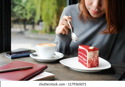 Asian women using a stainless spoon to eat a red velvet cake,Relax time with enjoy eating sweet