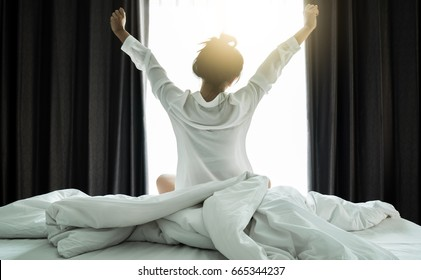 Asian women wake up from sleep. are  stretch herself  in the morning on the weekend sit on the bed at luxury room in Relax and weekend concept