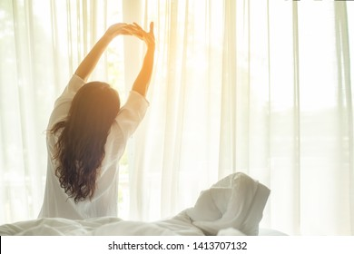 Asian women waking up stretching in bed room at home, early morning and sunny day.  Lifestyle Concept